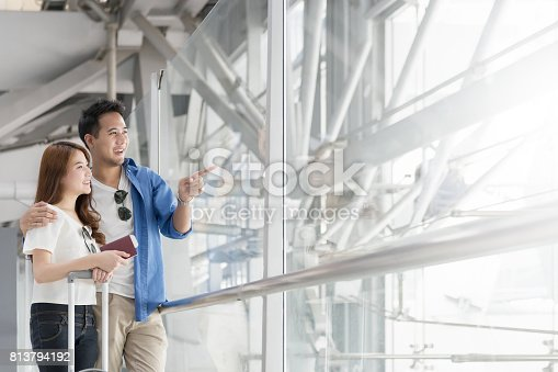 842907838 istock photo Couple asian student traveler looking outside and waiting for flight at airport terminal. Teenager are traveling concept. 813794192