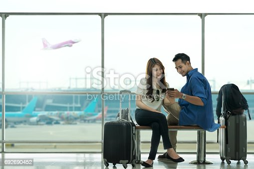 842907838 istock photo Couple asian student traveler looking smartphone and sit waiting for flight at airport terminal. Teenager are traveling concept. 692690452