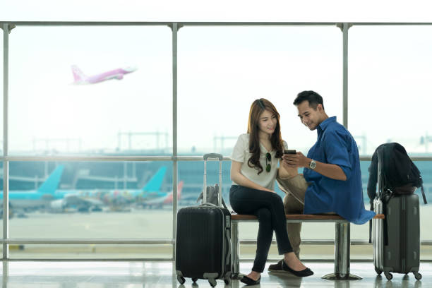 Couple asian student traveler looking smartphone and sit waiting for flight at airport terminal. Teenager are traveling concept. stock photo