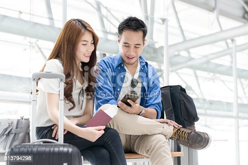 842907838 istock photo Couple asian student traveler looking smartphone and sit waiting for flight at airport terminal. Teenager are traveling concept. 813794298