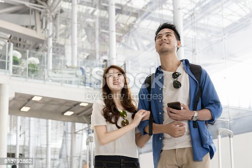 842907838 istock photo Couple asian student traveler looking up and find for flight at airport terminal. Teenager are traveling concept. 813793862