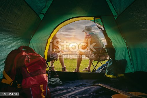 627343204 istock photo Couple asian travel camping together in forest, Happy and relax young man and woman sitting on chairs near tent with backpack,guitar looking mountain romantic rear view. 991354700