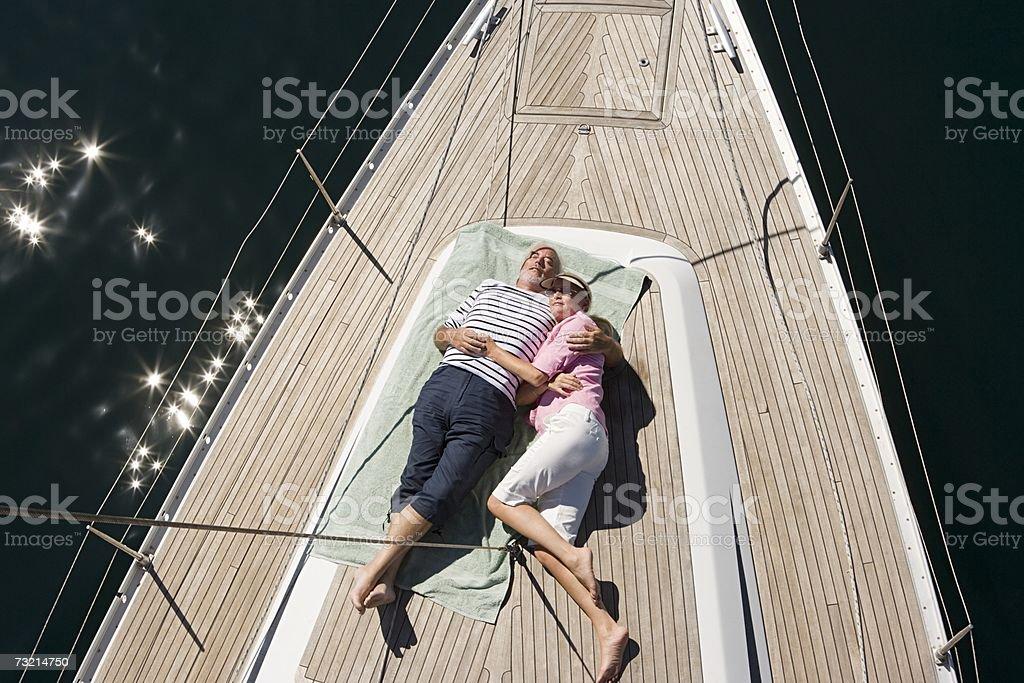 Couple asleep on deck of sailboat stock photo
