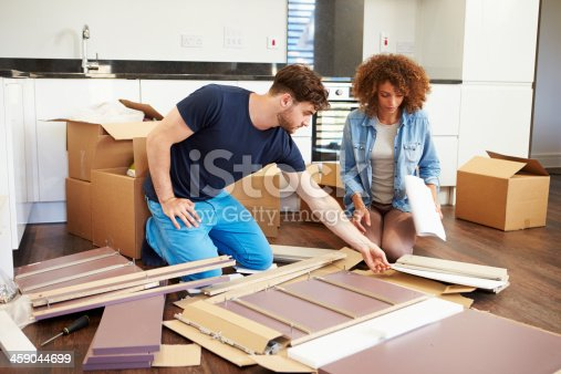 459373065 istock photo Couple assembling furniture in new home 459044699