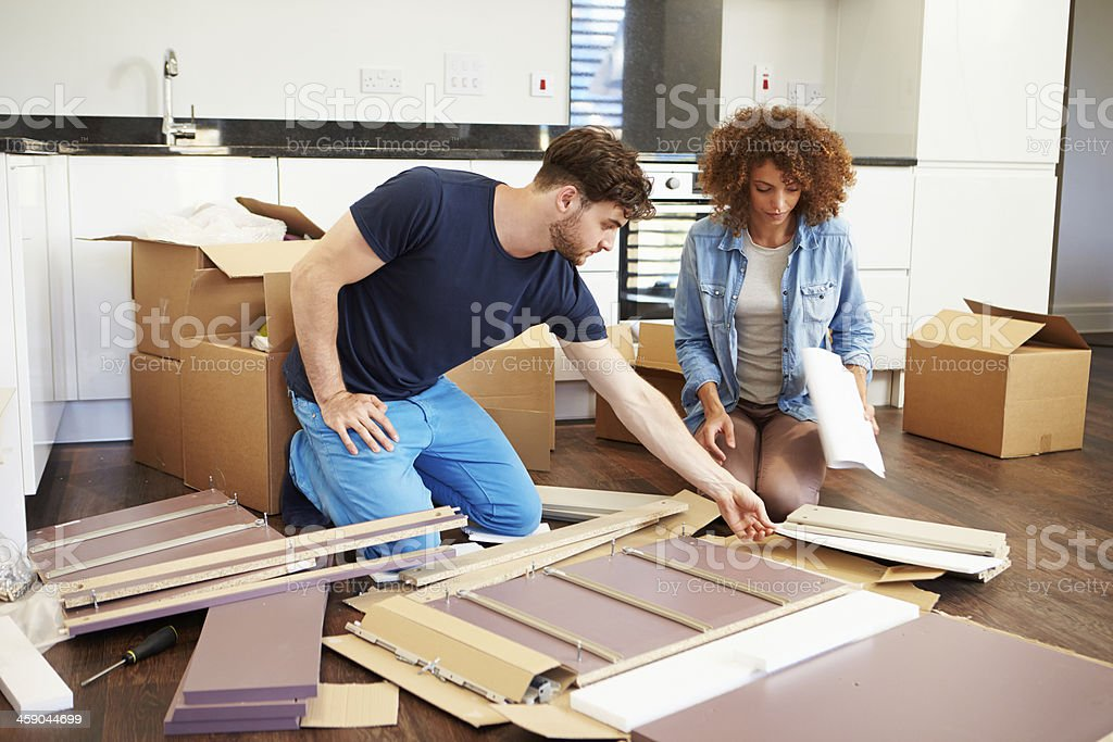 Couple assembling furniture in new home stock photo