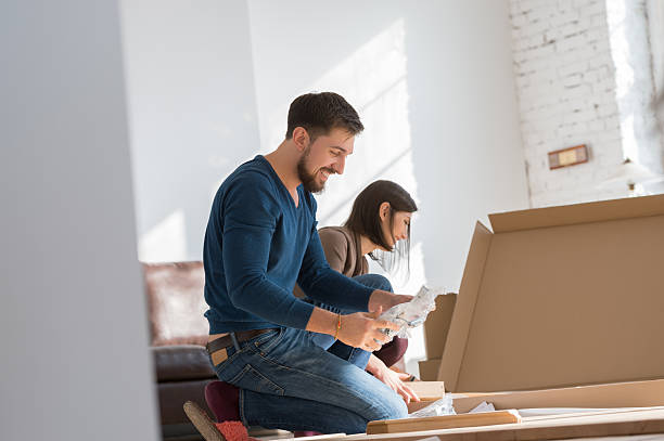 Couple assembling furniture in new house stock photo