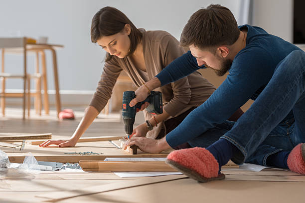 Couple assembling furniture in their new house stock photo
