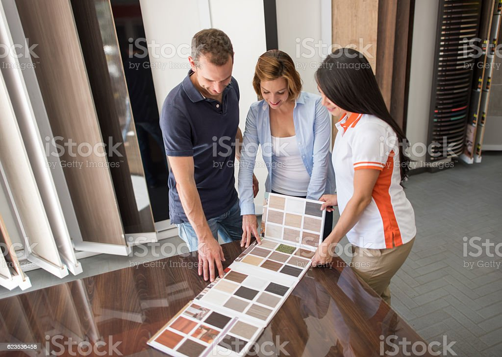 Couple at a floor store looking at wood samples stock photo