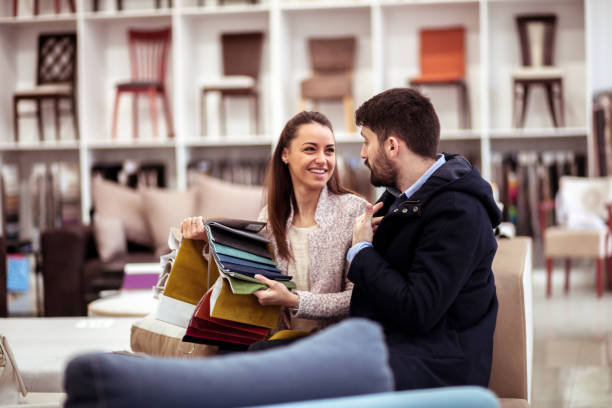 couple at a furniture store choosing fabrics - furniture shopping stock photos and pictures