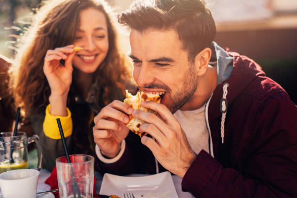 Couple at a restaurant Man eating a tortilla with his girlfriend at a restaurant. female sandwich stock pictures, royalty-free photos & images