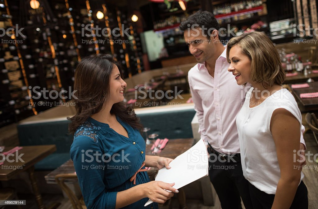 Couple at a restaurant talking to the hostess stock photo