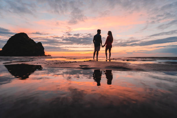 Couple at beach holding hands and looking at each other. stock photo