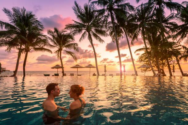 Pärchen Sie sich an den Strandurlaub, entspannen Sie sich im Pool mit einer malerischen tropischen Landschaft bei Sonnenuntergang, romantischer Sommer-Flitterwochen-Inselort, Kokospalme am Meer – Foto