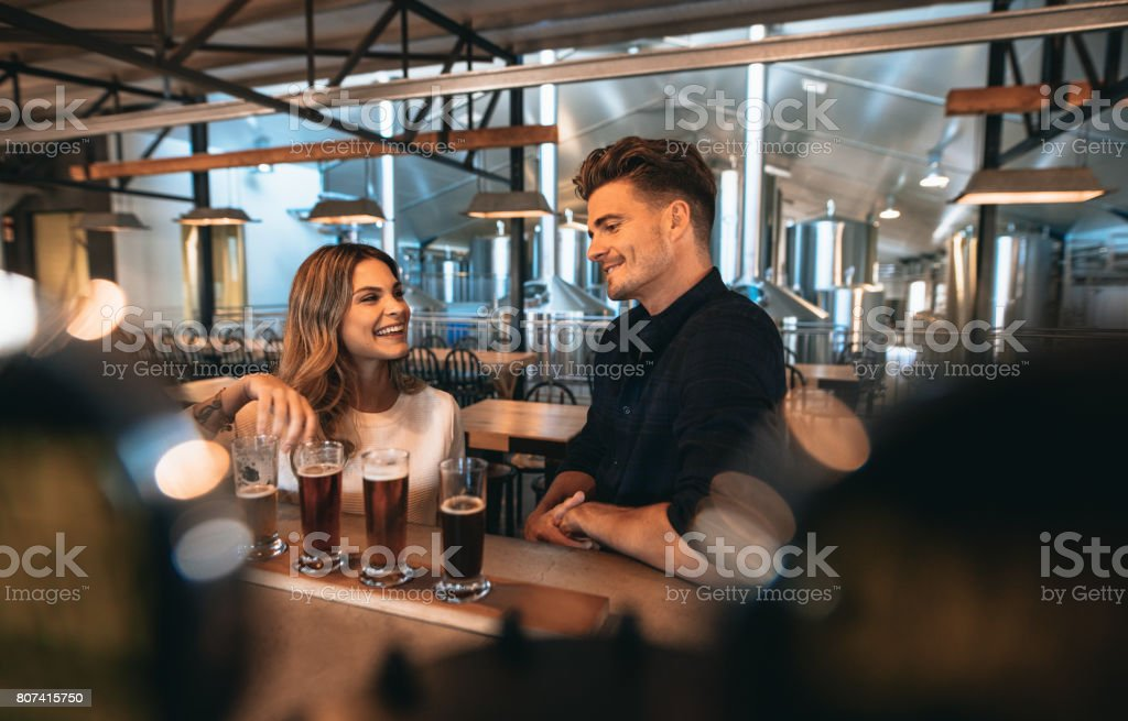 Couple at brewery bar and tasting beer - foto stock