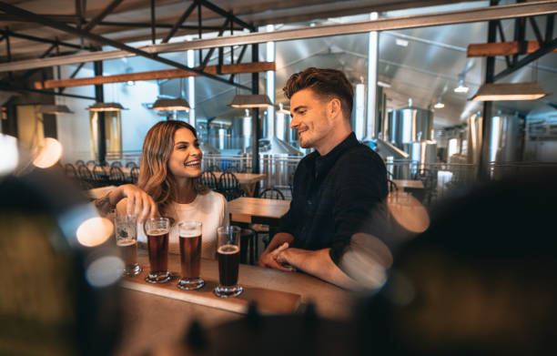 Couple at brewery bar and tasting beer stock photo
