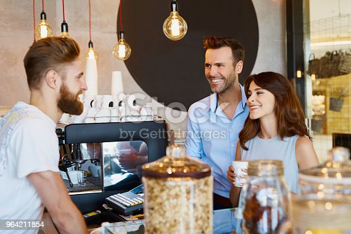 597640822 istock photo Couple at cafe talking barista, buying coffee 964211854