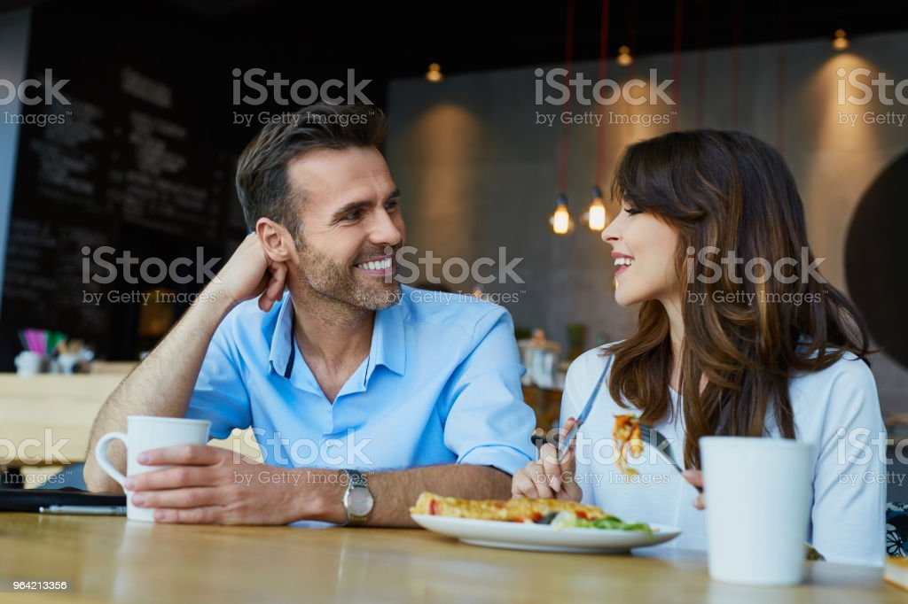 Couple at cafe talking during lunch stock photo