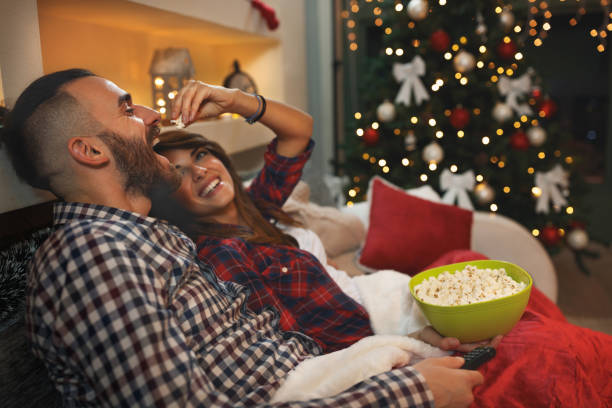 couple at christmas eve enjoy with popcorn while watching tv - christmas movie foto e immagini stock