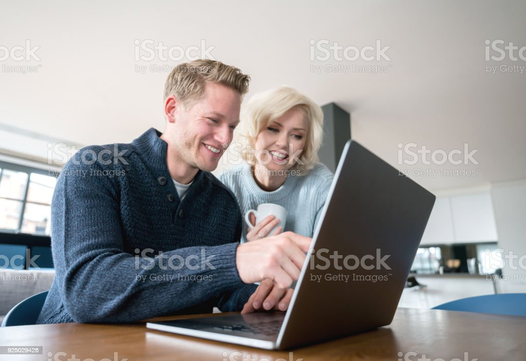 Couple at home and man pointing at something on the laptop's screen to his girlfriend both looking happy stock photo