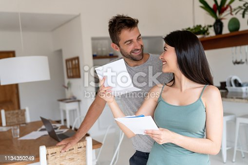 istock Couple at home looking happy checking their mail 1134350249
