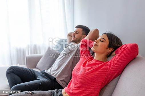 938682762istockphoto Couple at home relaxing in sofa. 1143762389