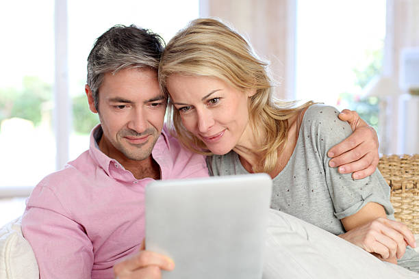 Couple at home using electronic tablet stock photo
