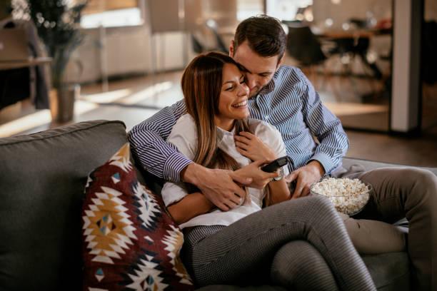 pareja en casa viendo la televisión - couple fotografías e imágenes de stock