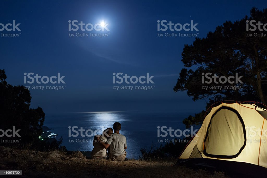 Couple at moon night near tent stock photo