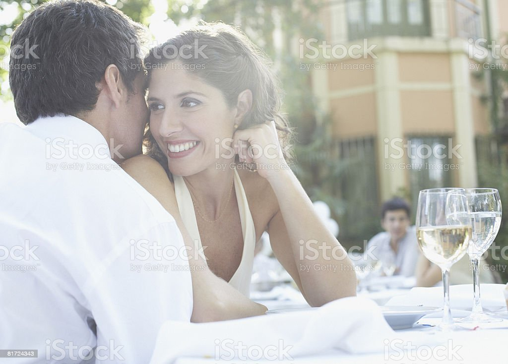 Couple at outdoor party whispering and smiling stock photo