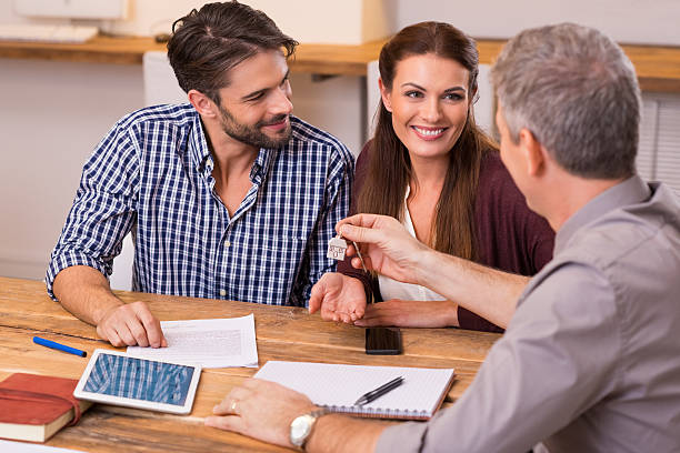 couple en agence immobilière - prêts immobiliers et crédits photos et images de collection