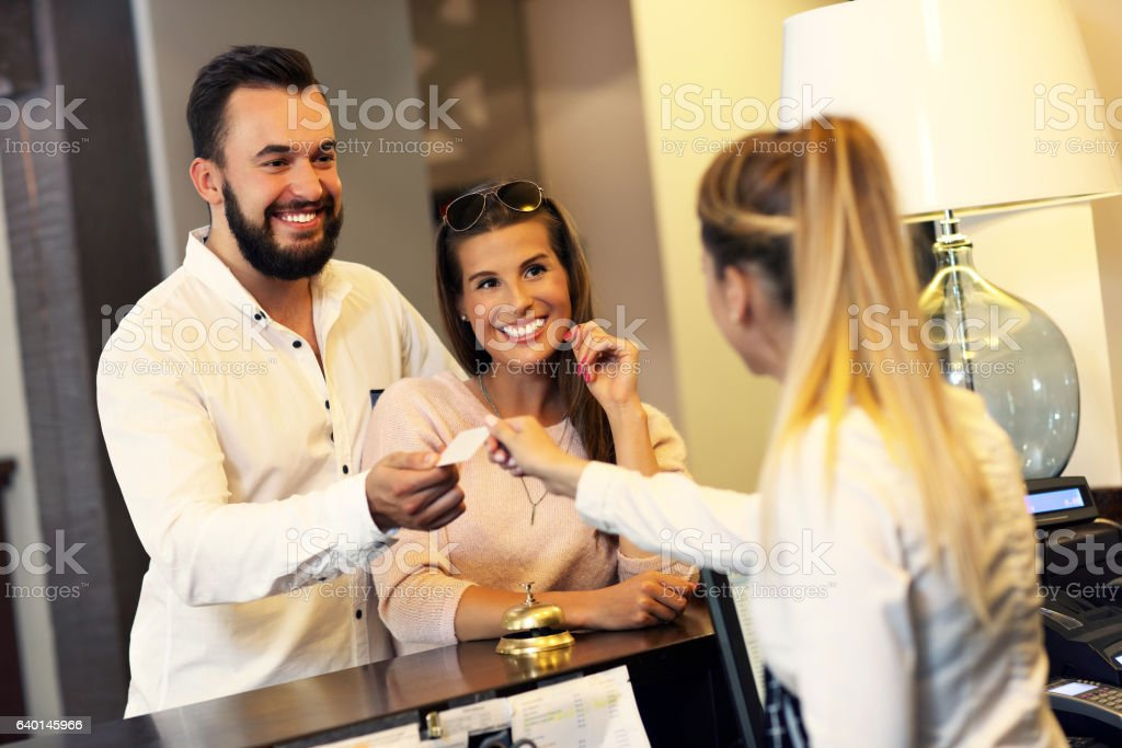 Couple at reception desk in hotel stock photo