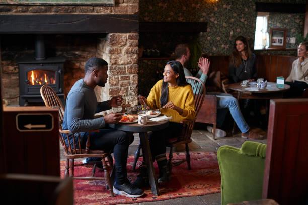paar am tisch in traditionellen englischen pub essen frühstück - liebeskummer englisch stock-fotos und bilder