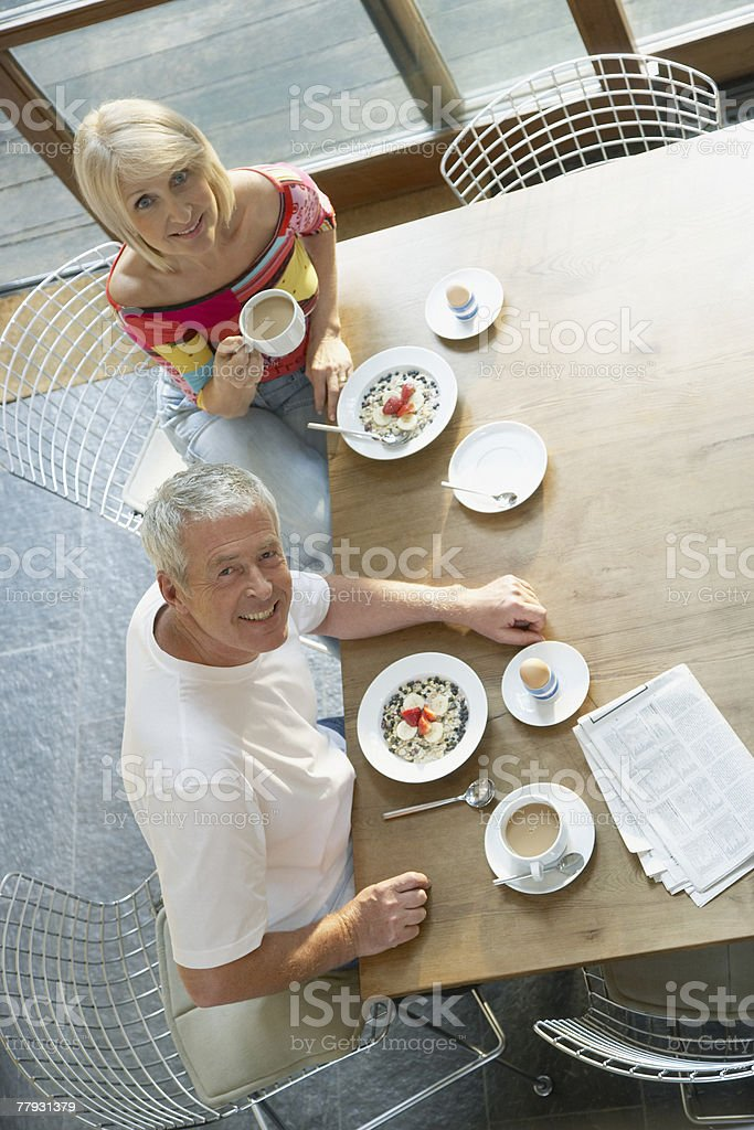 Couple at table with breakfast and newspaper royalty-free stock photo
