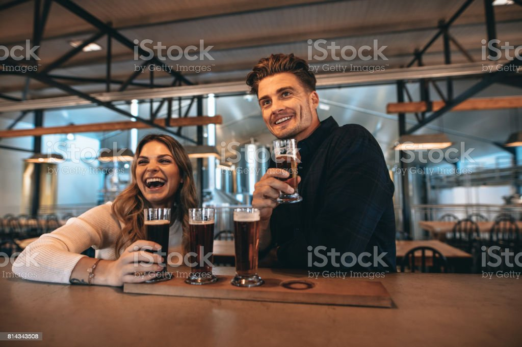 Couple at the bar with different varieties of craft beers stock photo