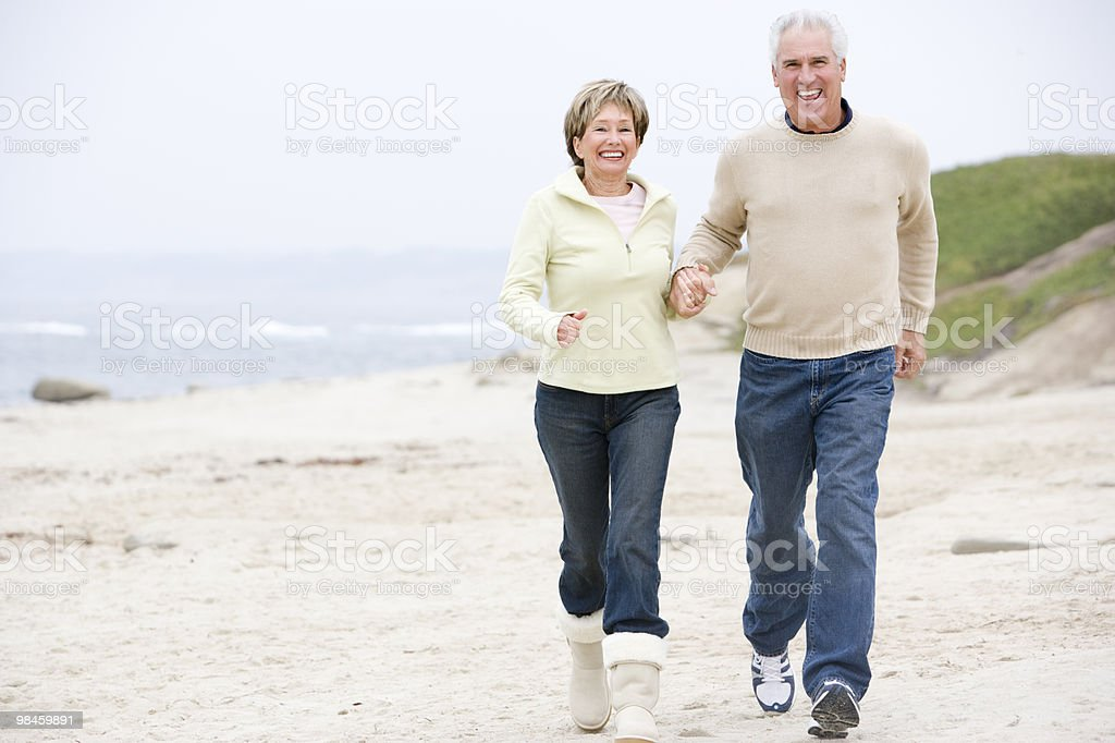 Couple at the beach holding hands royalty-free stock photo