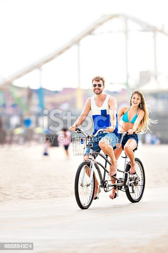 Couple riding tandem bicycle at the beach in Los Angeles