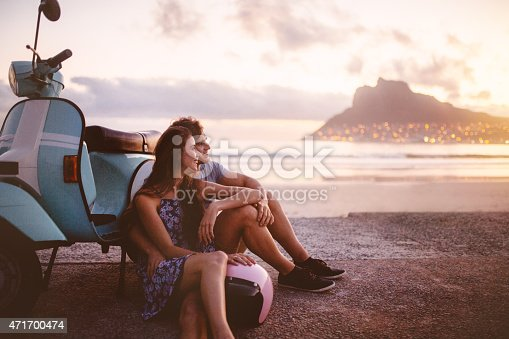 Young couple at the beach sitting next to their scooter and looking out at the sea