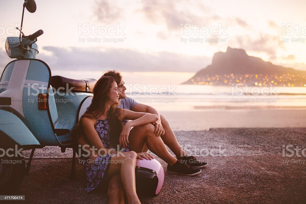 Pareja en la playa con un scooter con vista al mar - foto de stock