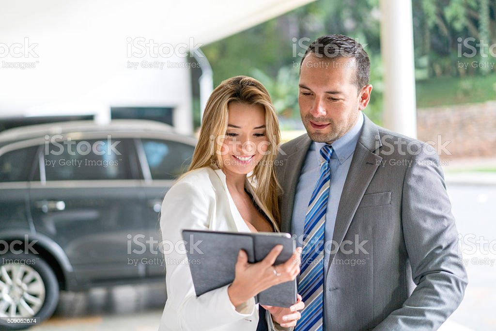 Couple at the car dealership stock photo