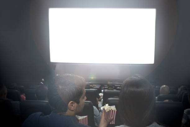 Couple at the cinema looking at a white screen stock photo