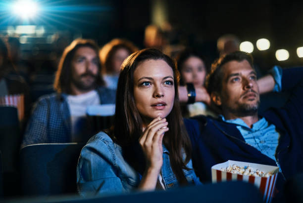 Couple at the movies Close up of a couple enjoying a movie in the cinema movie stock pictures, royalty-free photos & images