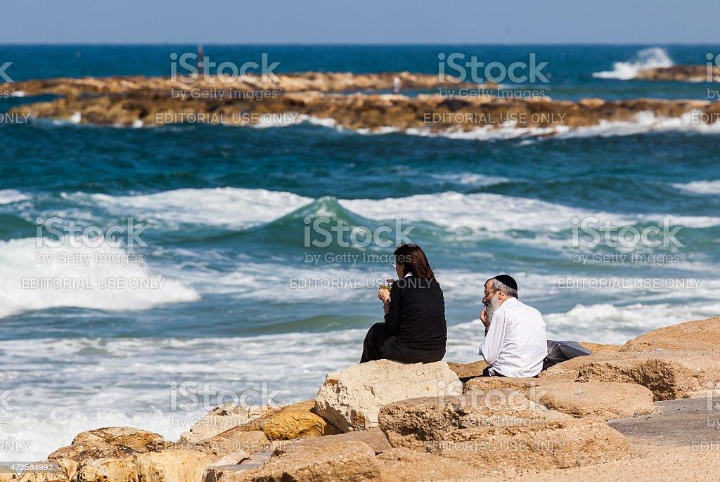 Couple at the seashore enjoys the view. Tel Aviv, Israel stock photo