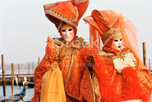 istock Couple at the Venice Carnival with orange costumes and masks 529047271