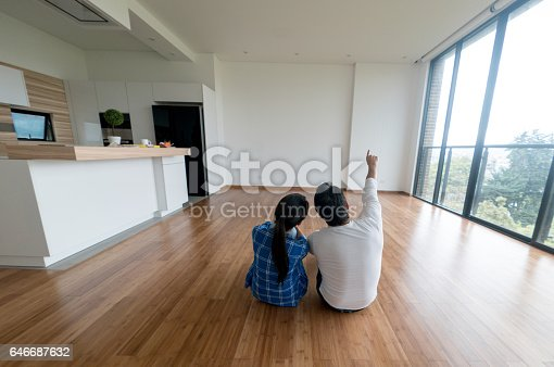Loving couple at their new home sharing ideas about how to decorate it - real estate concepts