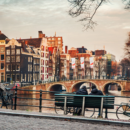 Amsterdam - December 7, 2015: Couple back portrait sitting on a bench at sunset in Amsterdam