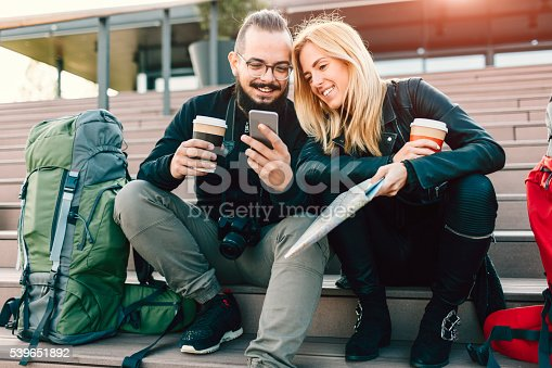 istock Couple Backpackers Sitting On Stairs And Using Smart Phone. 539651892