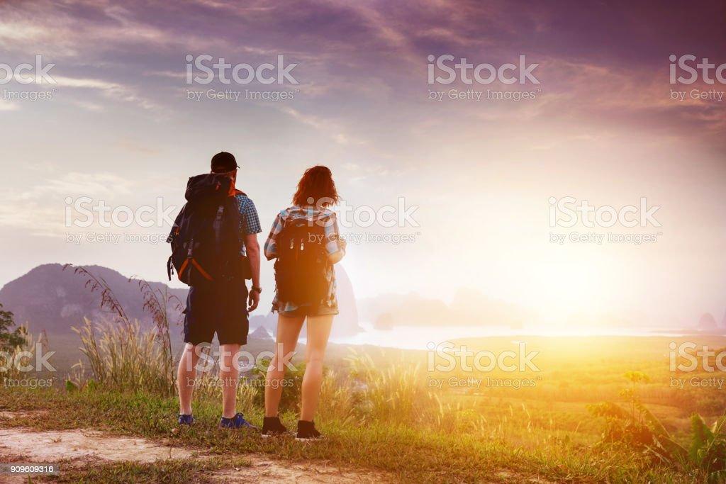 Mochileros par ver al amanecer o atardecer cerca de la bahía del mar y las islas - foto de stock
