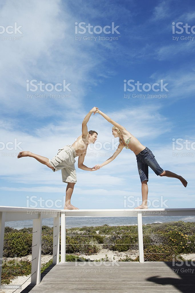 A couple balancing on the rail of a terrace stock photo