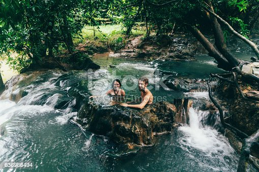 Young Caucasian couple bathing in hot spring waterfall in Thailand