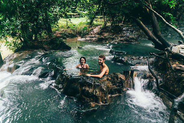 couple bathing in hot spring waterfall - hot spring stock photos and pictures